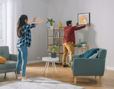 Couple hanging a picture in their newly decorated living room